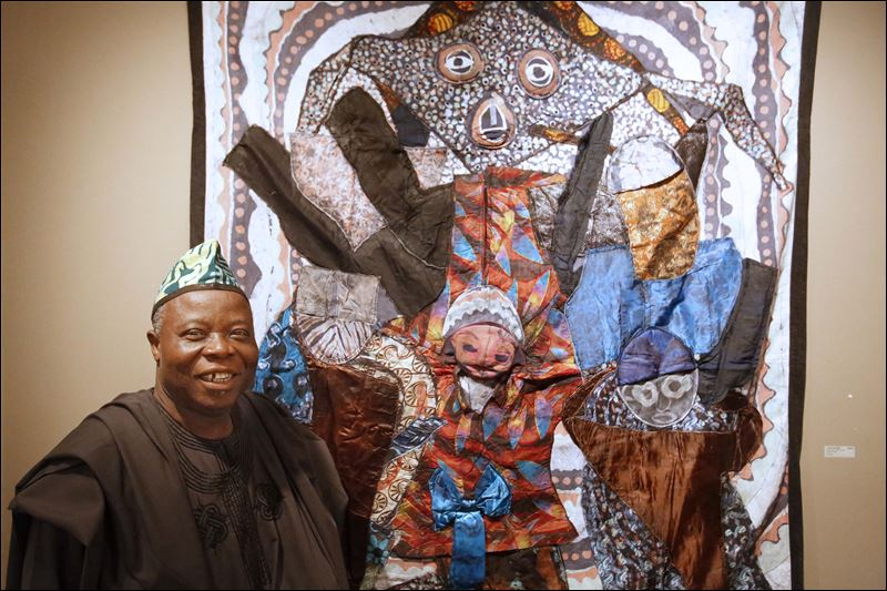 Tunde stands with one of his batik quilts at the Hudson Gallery in Sylvania, Ohio. Photo: Toledo Blade/Katie Rausch